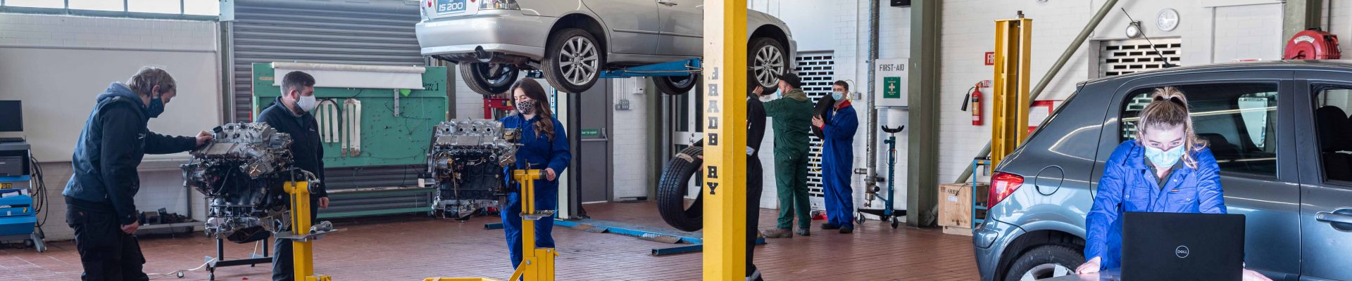 Light vehicle apprentice technicians in car maintenance workshop